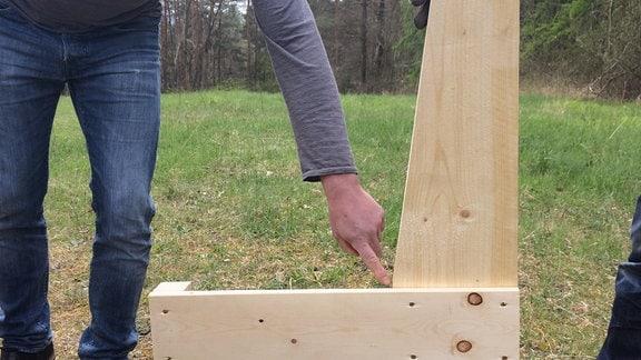 Eine Männerhand hält eine Holzkonstruktion. Ein anderer Mann zeigt auf eine Stelle an der Konstruktion.