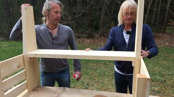 Zwei Männer halten ein Brett und eine Holzkonstruktion.