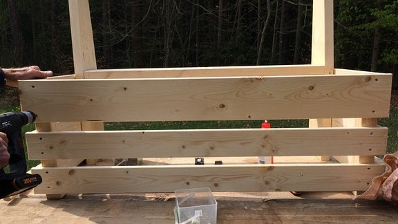 Blick von vorn auf eine Holzkiste, die sich im Entstehungszustand befindet.