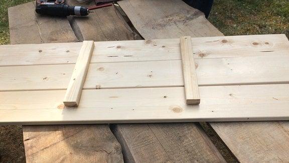 Auf einem Tisch liegen drei lange Bretter die mit zwei kleinen Hölzern an einander fixiert sind. Im Hintergrund ist Werkzeug zu erkennen.