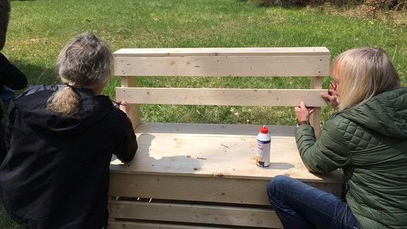 Zwei Männer knien mit dem Rücken zur Bank vor einer Bank aus Holz.