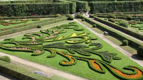 Mit präzise geschnittenen Pflanzen wurden Ornamente auf Beeten angelegt, die teilweise mit farbigen Blumen gefüllt sind.