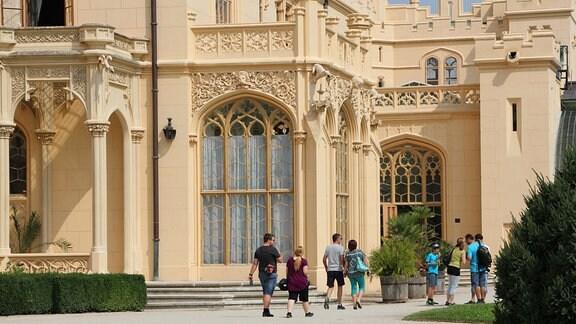 Menschen laufen vor einem prunkvollen Haus entlang