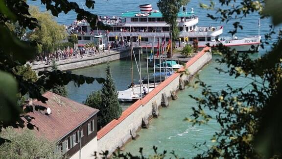 Steg im Bodensee mit Schiff und Booten.