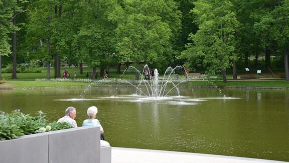 Zwei ältere Menschen sitzen an einem Teich. In der Mitte des Teiches ist ein Springbrunnen.