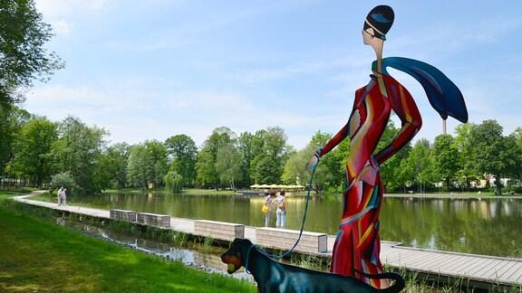 Eine Skulptur Frau mit Dobermann steht an einem Teich mit Steg.