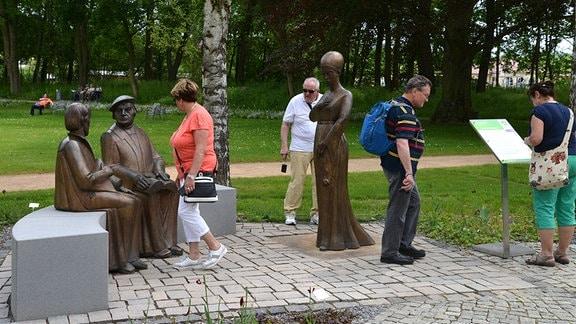 Menschen spazieren auf einer Promenade in einem Park.