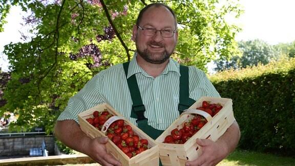 Ein Mann mit grüner Latzhose hält zwei Erdbeerkörbe in den Armen.