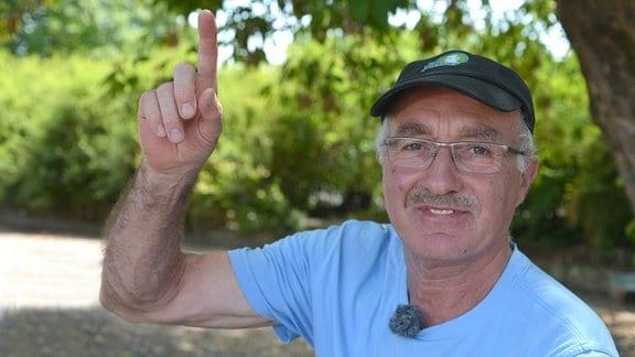 Ein Mann mit Brille und Schirmmütze hebt einen Finger.