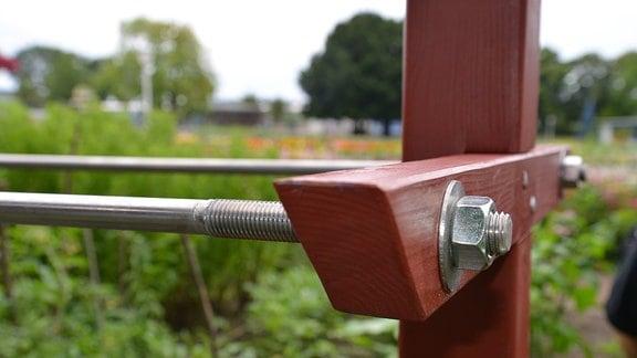 Lange Stahlrohre wurden mit einem Holzbalken verschraubt.