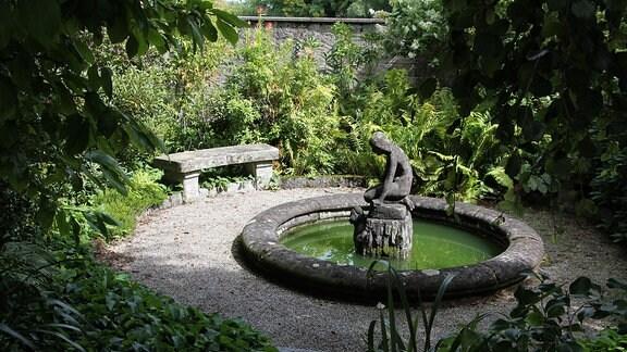 Brunnen mit Bank auf einem Platz inmitten eines Gartens