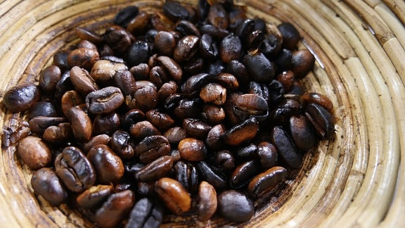 Geröstete, dunkle Kaffeebohnen in einer Schale.