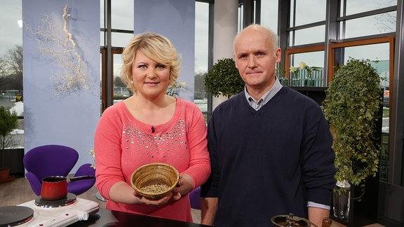Eine Frau und ein Mann stehen hinter einem Tisch. Die Frau hält eine Schale in der Hand, in der helle Kaffeebohnen liegen.