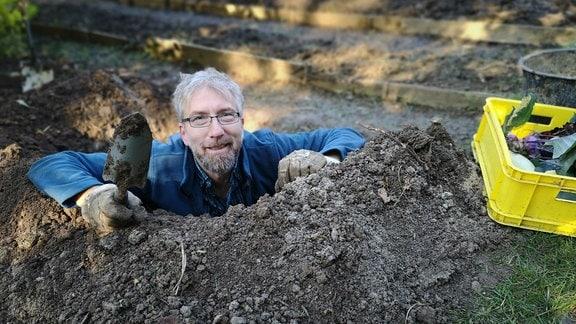 Regisseur Jörg Heiß steht in einem tiefen Erdloch und hält eine kleine Schaufel in der Hand.