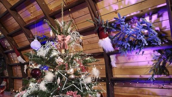 Geschmückter Weihnachtsbaum in einem gemütlichen Raum.