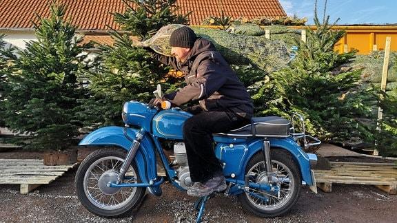 Mann sitzt auf dem Mottorrad und transportiert einen Weihnachtsbaum auf der Schulter.