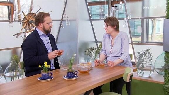 Zwei Menschen sitzen bei einer Tasse Tee zusammen.
