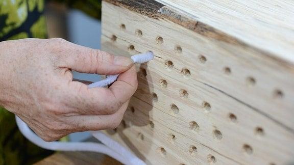 Ein Holzblock in dem viele Löcher gebohrt sind. Mit einer langen Bürste werden die Röhren gereinigt.