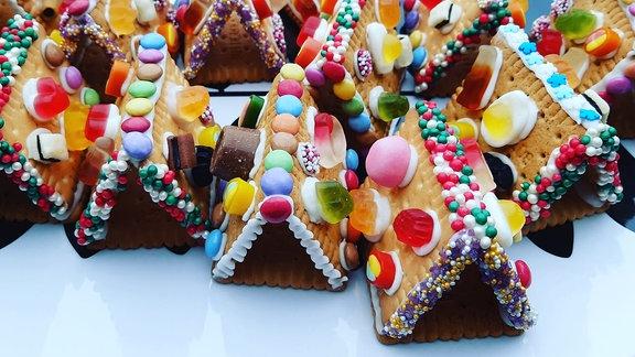 Aus drei Keksen gebaute und mit Süßigkeiten garnierte Häuser.