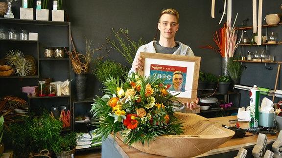 Florist Martin Neumann zeigt seine Urkunde