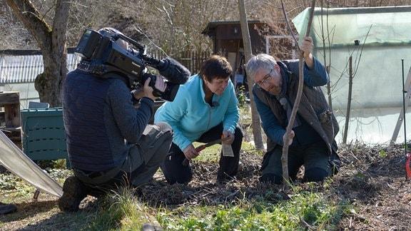 Obstbauexpertin Monika Möhler und Hobbygärtner Jörg Heiß werden von einem Kameramann in einem Garten gefilmt.
