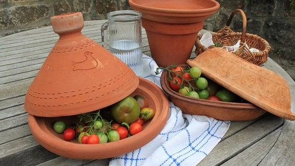 Unreife Tomaten in Tongefäßen mit Deckel.