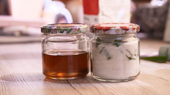 Zwei Gläser auf einem Tisch. In einem Glas befindet sich ein Saft, in dem anderen Blätter und Zucker.