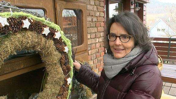 Gartenbauingenieurin Ilka Hoffmann zeigt einen großen Kranz der mit Zapfen und Sternen geschmückt ist