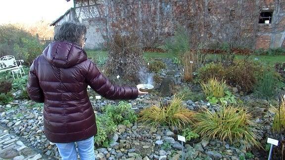 Eine Frau geht mit einer Räucherschale durch den Garten