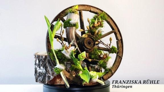 altes Kutschenrad mit Pflanzen dekoriert