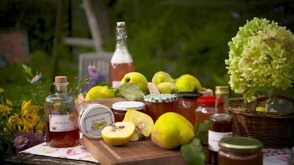 Quitten und Produkte aus Quitten stehen auf einem Tisch.