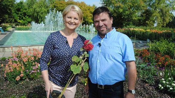 MDR Garten-Moderatorin Diana Fritzsche-Grimmig steht mit einer gefüllt rot blühenden Stockrose im Topf neben Sebastian Albrecht vom Eichsfelder Staudenhof im Erfurter Egapark