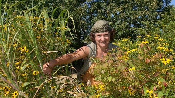 Eine Frau schaut durch verschiedene hochwachsende Pflanzen hindurch.
