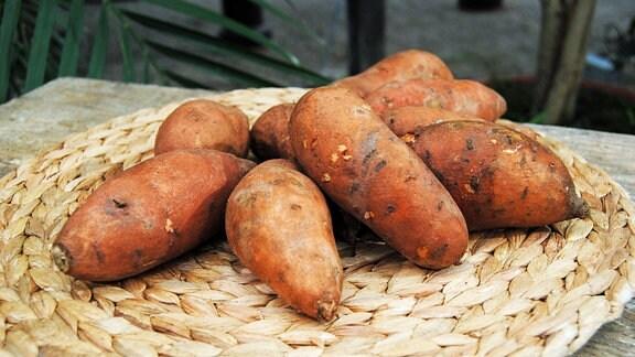 Mehrere Süßkartoffel-Knollen liegen auf einem flachen, geflochtetenen Teller