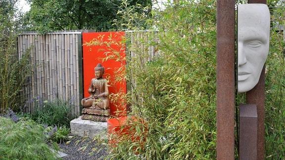 Ein Garten mit Blick auf einem Sichtschutzzaun aus dicken Bambusrohren. Vor dem Zaun befindet sich eine Buda-Figur. Im Vordergrund wächst Bambus.