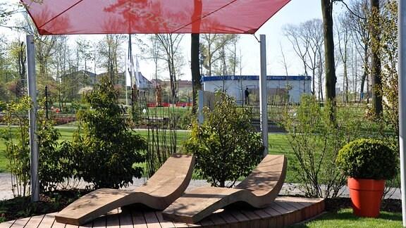 Eine Insel in einem Garten aus Holz. Auf der kleinen mit einem Sonnensegel überdachten Fläche stehen zwei Holz-Sonnenliegen.