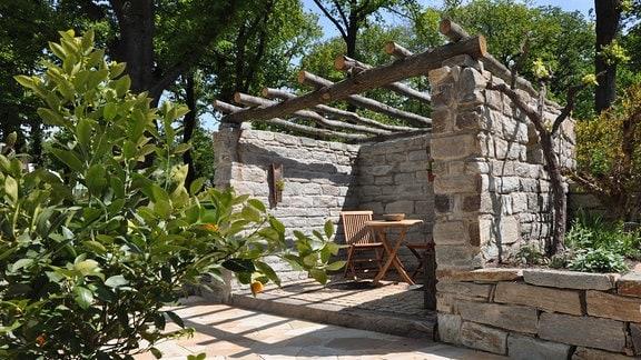 Aus Naturstein gemauerte Pergola mit einer Decke aus ungeschältem Rundholz.