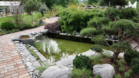 Ein gepflasterter Teich führt an einem kleinen Gartenteich vorbei.
