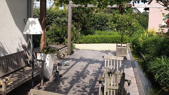 Terrasse aus Holz mit einer Pergola an die eine Kiesfläche anschließt. Auf der rechten Seite zieht sich ein langer Wassergraben über das Grundstück.