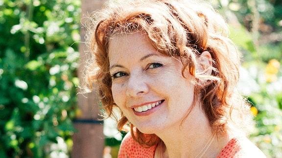 Eine Frau steht in einem Garten. In der Hand hält sie einen kleinen Strauß aus Kräutern.