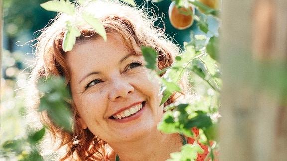 Eine Frau mit grüner Schürze steht in einem Garten vor einem Pfirsichbaum mit Früchten.