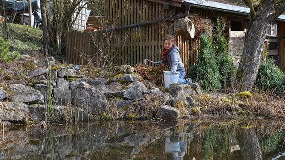 Gärtnerin Brigitte Goss arbeitet an einem Teich