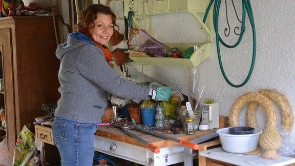 Gärtnerin Brigitte Goss steht an der Werkbank in ihrer Sommerküche