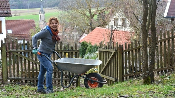 Gärtnerin Brigitte Goss schiebt eine Schubkarre