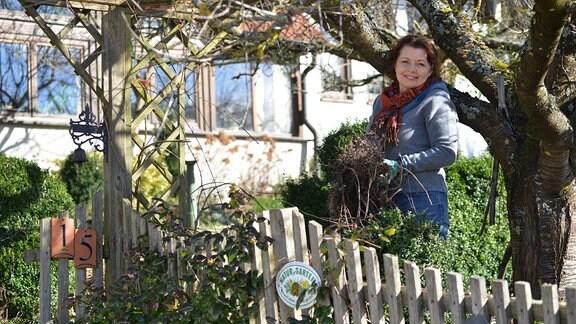 Gärtnerin Brigitte Goss steht in ihrem Garten