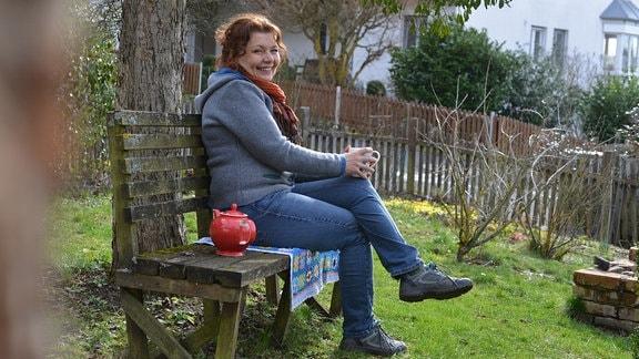 Gärtnerin Brigitte Goss sitzt auf einer Bank in ihrem Garten