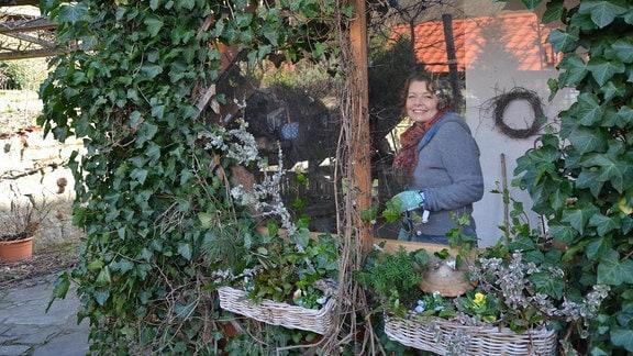 Gärtnerin Brigitte Goss steht in einem Wintergarten