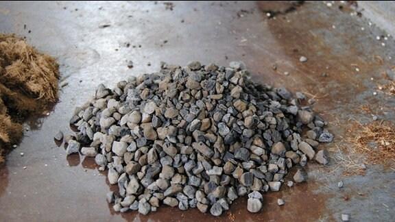 Ein Häufchen braun-grauer Schiefersteinchen auf einer Metallplatte
