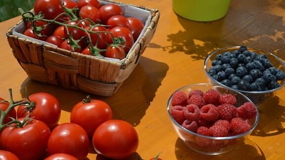 Tomaten, Heidelbeeren und Himbeeren stehen auf einem Tisch