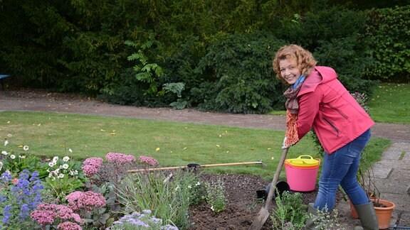 Eine Frau arbeitet auf einem Beet und gräbt Pflanzen ein. Auf dem Beet wachsen verschiedene Pflanzen.